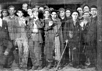 Hollow-eyed, emaciated male prisoners, victims of Nazi genocide against Jews of Europe & others, gripping barbed wire fence in wonderment at their liberation by Amer. forces from the cruelties of Buchenwald concentration camp. (Photo by Margaret Bourke-White//Time Life Pictures/Getty Images)